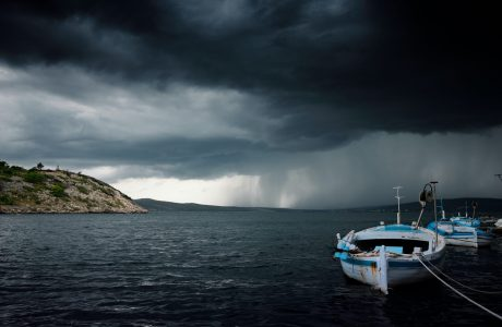 black storm clouds over boats moored at beach